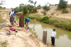 Kenya Water Resources Management Authority workers build a water quality monitoring station on the Mwache River.Photo courtesy of the Mwache Dam Project