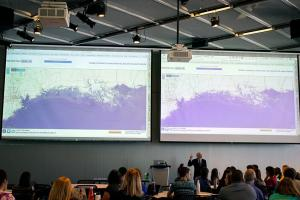 "Professor John Sterman displays maps showing the consequences of sea-level rise on various coastal cities, as part of the ""SimPlanet"" event at MIT.Images: Melanie Gonick, MIT"